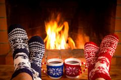 Couple in Christmas socks near fireplace Stock Photography