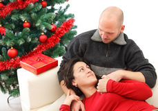 Couple at Christmas time. Romantic young couple looking one to another near the Christmas tree Royalty Free Stock Photos