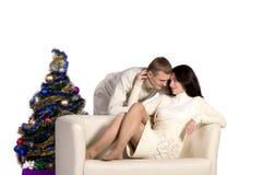 Couple at Christmas tree next to a white sofa Royalty Free Stock Photos