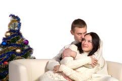 Couple at Christmas tree next to a white sofa Royalty Free Stock Photo