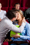Couple in cinema with popcorn kissing Royalty Free Stock Images