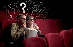Couple in cinema with questions. Nice couple in cinema with drawn question signs around stock photography