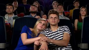 Couple in cinema watching a movie, and kissing stock video footage