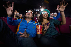 Couple in cinema wearing 3D glasses, smiling, low angle view Stock Photos