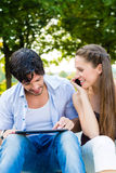 Couple in city park with tablet computer Stock Photo