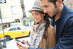 Couple in city streets using smartphone Royalty Free Stock Image
