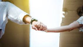 Couple clasp hand together. Couple , smart man and beautiful woman clasp hands behind is sunlight in the evening. lover wedding concept stock photography