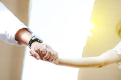 Couple clasp hand together. Couple , smart man and beautiful woman clasp hands behind is sunlight in the evening. lover wedding concept stock images