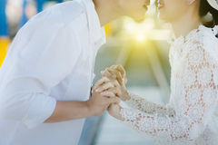 Couple clasp hand together. Couple , smart man and beautiful woman clasp hands behind is sunlight in the evening. lover wedding concept stock photo