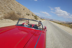 Couple In Classic Car On Desert Road Stock Photography