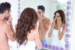 Couple cleaning face while looking in mirror. Young couple cleaning face while looking in mirror at bathroom royalty free stock photo