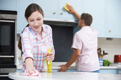 Couple Cleaning Kitchen Surfaces And Cupboards Together Stock Photos