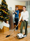 Couple cleaning with vacuum cleaner Royalty Free Stock Photos
