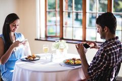Couple clicking photo of a food on plate. In restaurant stock images