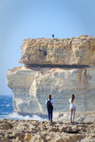 Couple on the cliffs of Azur Window, Gozo, Malta.  Royalty Free Stock Photo