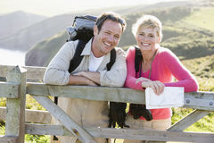 Couple on cliffside outdoors leaning on railing Royalty Free Stock Photography