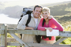 Couple on cliffside outdoors leaning on railing Stock Photo
