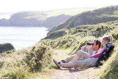 Couple on cliffside outdoors using binoculars Royalty Free Stock Photos