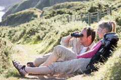 Couple on cliffside outdoors using binoculars Stock Photos