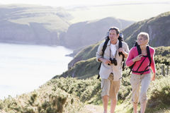 Couple on cliffside outdoors walking and smiling royalty free stock image