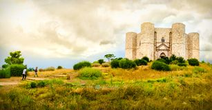 Couple climb steps in a natural yellow landscape to reach  Castel del Monte in Apulia - Andria Trani province - Italy Royalty Free Stock Photo