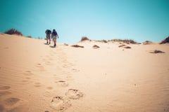 Couple climbing sand dunes stock image