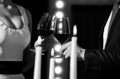 Couple clink glasses with red wine at meeting or wedding. Couple clink glasses with red wine at meeting or date in formal outfit in restaurant, celebration and stock photos
