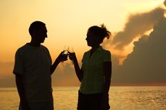 Couple clink glasses. Silhouettes against sea. Royalty Free Stock Photos