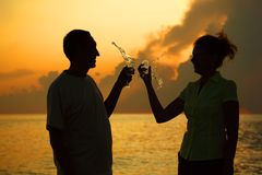 Couple clink glasses. Splashes of wine. Stock Photo