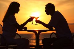 Couple clink glasses on sunset outside Stock Images