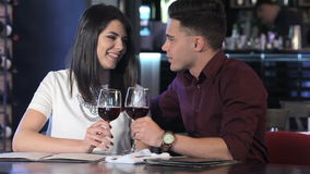 Couple clink their glasses. Caucasian couple clinking their glasses with wine at the restaurant. Young man and woman smiling for the camera. Man with brown watch stock video