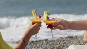 Couple clinking glasses of cocktail on beach in front of sea stock footage