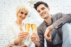 Couple clinking with sparkling wine for Christmas royalty free stock image