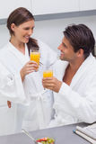 Couple clinking their glass of orange juice Stock Photos