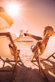 Couple clinking their glasses while relaxing on their deck chairs Royalty Free Stock Photos