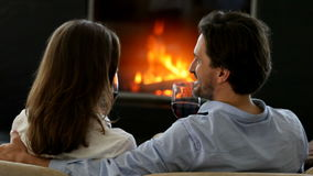 Couple clinking wine glasses. Happy couple clinking red wine glasses near fireplace stock footage