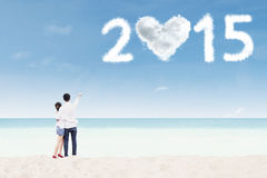 Couple with cloud shaped number 2015 Stock Photography