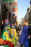 Couple of clown masks sitting and smiling inVittorio Emanuele main street during Carnival. Stock Image