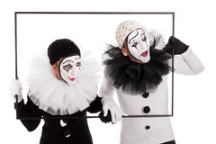 Two clowns in a frame looking in the same direction Stock Image
