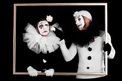 Two clowns in a frame, one looks sorrowful. Couple of clowns in a frame, one looks sorrowful Stock Photography