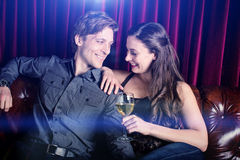 Couple at a club. Young flirty couple with wine at a club lounge Royalty Free Stock Image