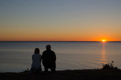 Couple at the coast by sunset Royalty Free Stock Image