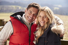 Couple in coats embracing in the countryside look to camera Royalty Free Stock Photography