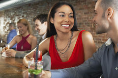 Couple With Cocktails At Bar. Happy multiethnic couples with cocktails sitting at the bar Stock Images