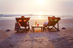 Couple with cocktails relaxing on the beach. At sunset Stock Photo