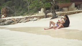 Couple With Coconut Drink Relaxing On The Beach. Slow motion shot of a young couple with coconut drink relaxing on the beach in the summer day stock video footage