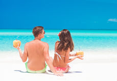 Couple with coconuts in hands having fun at Stock Photography