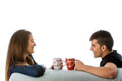 Couple with coffe mugs on couch. Close up portrait of young couple drinking coffee on couch.Isolated on white background Royalty Free Stock Photo