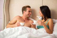 Couple with coffee in bed. Stock Photos
