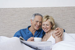 Couple With Coffee Cup Reading Newspaper In Bed Royalty Free Stock Photography